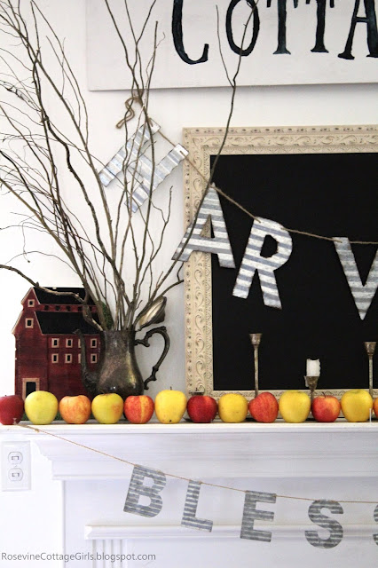Chalkboard on a mantel, red barn platter, silver coffee server with branches, apples on mantelMinimalist Farmhouse Apple Mantel