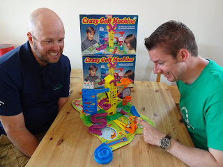 Steve Sheila Lovell and Richard Gottfried recreate the box art of the Crazy Golf Machine board game