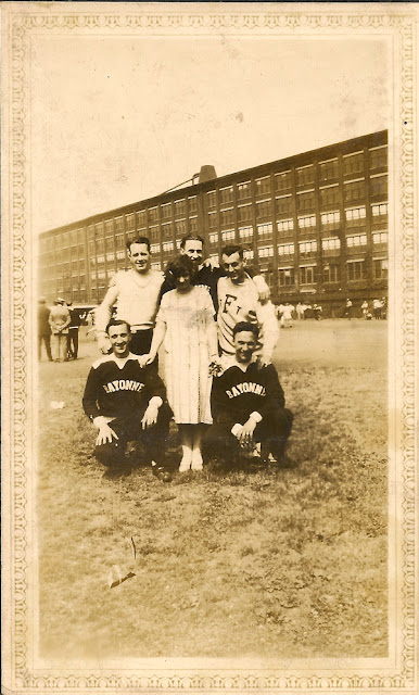 "Girl poses with 5 men at a sporting event. Some of the men wear ""Bayonne"" jerseys. Factory in the background."