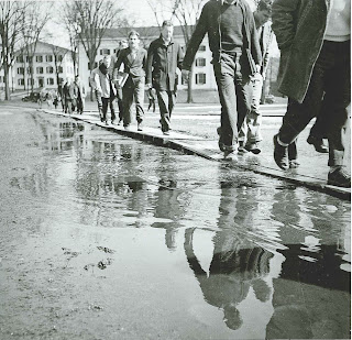 A series of men walking along boards to avoid standing water on the ground.