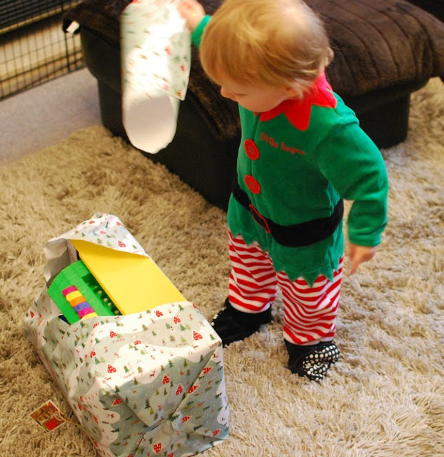 Our-First-Blogging-Christmas-picture-of-toddler-looking-at-present