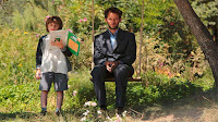 Pierre sentado en una hamaca junto con uno de los hijos de Louise que sostiene un cuaderno abierto en la mano