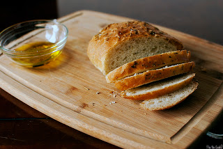 rosemary bread sliced on a cutting board with olive oil in a bowl