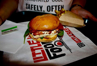 A white circular block with green lettuce and red sauce inside two golden buns on a white tray with a portion of rectangular golden fries next to it on a light brown square table with a guy wearing a white tshirt behind the burger on a dark background.