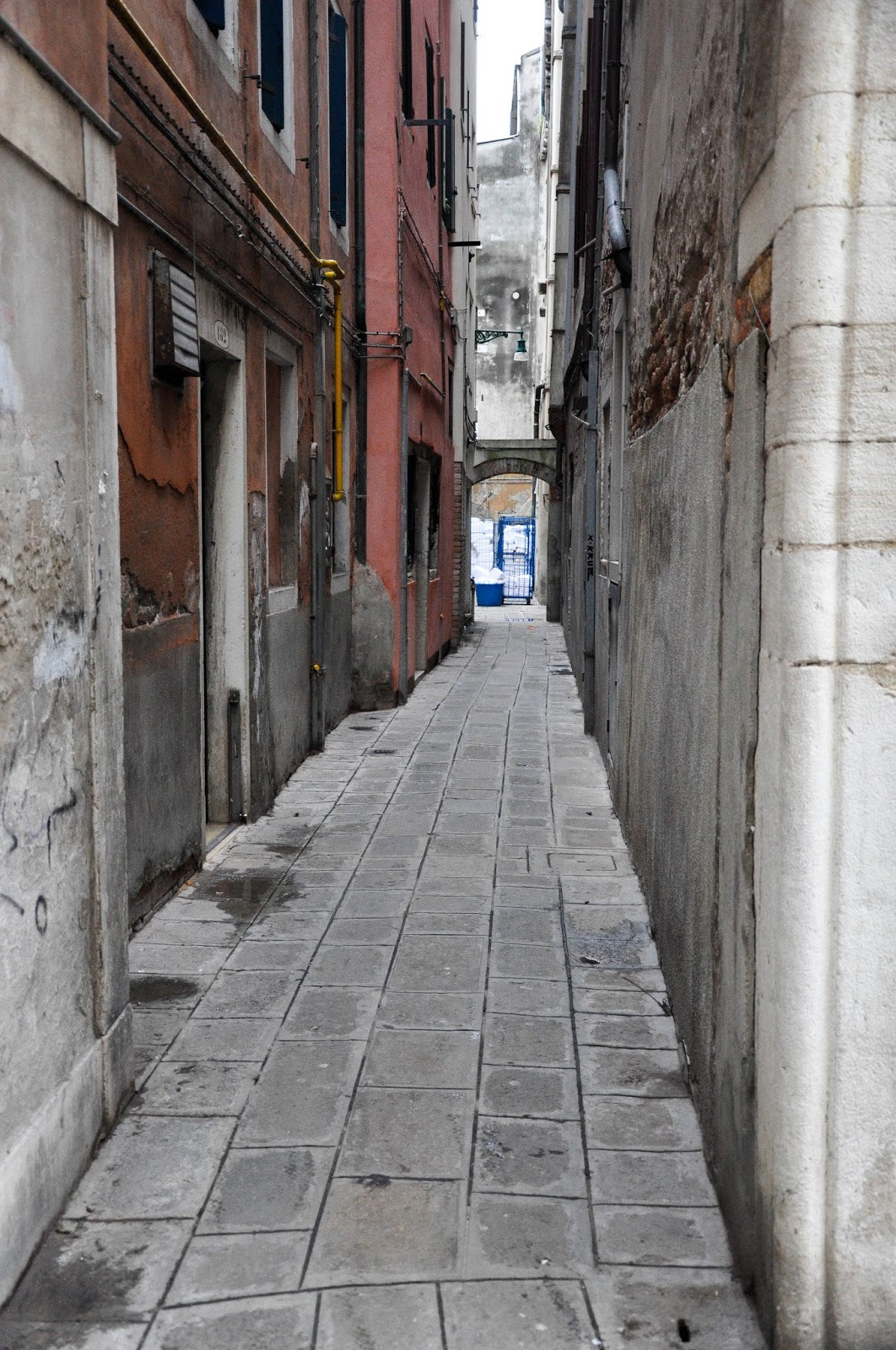 Empty side street with piles of freshly washed sheets at the far end, Venice, Italy