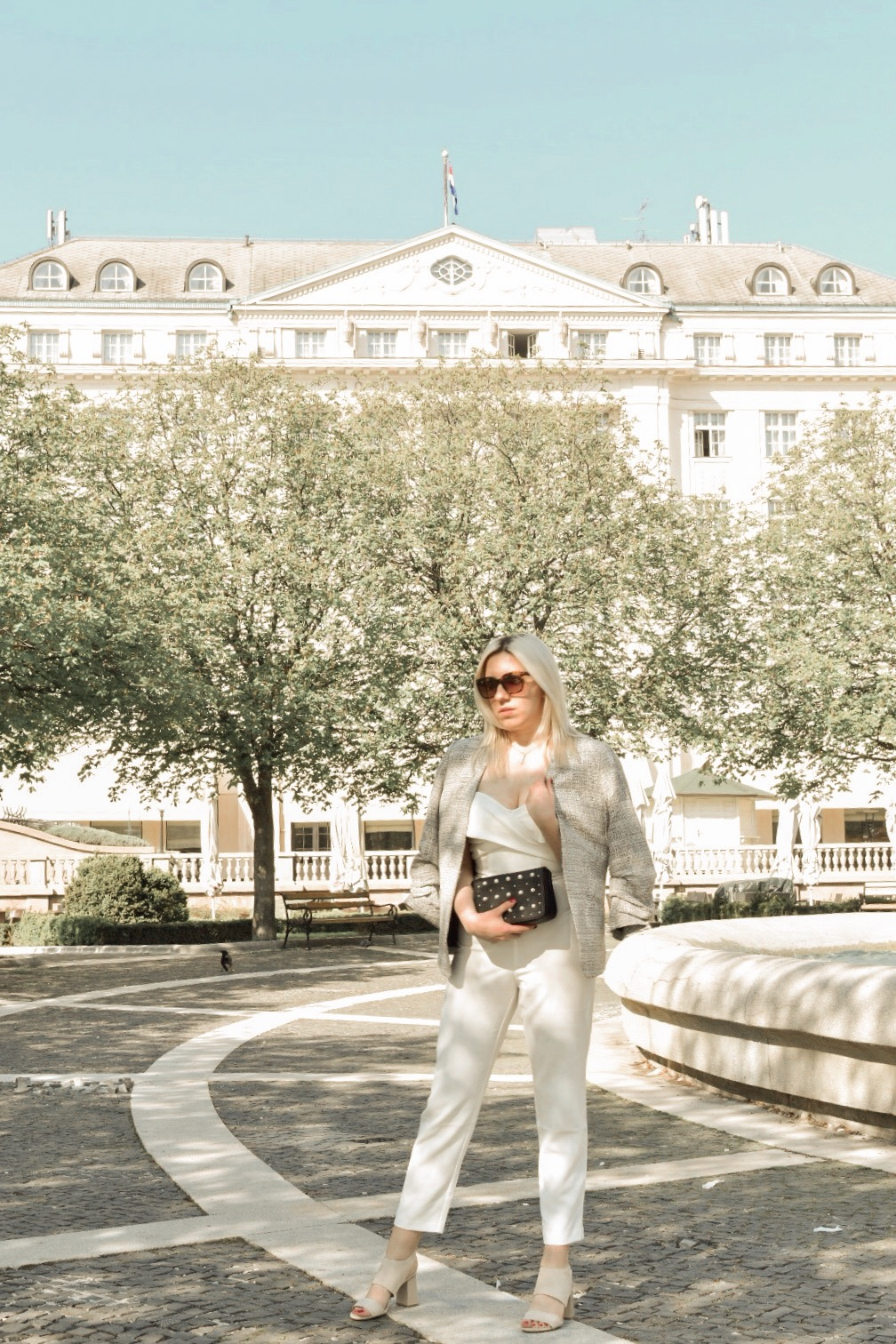 Fashion blogger in a white jumpsuit in front of the Esplanade hotel in Zagreb
