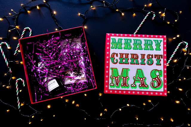 A Christmas themed box with thin strips of purple foil lametta half hiding the presents