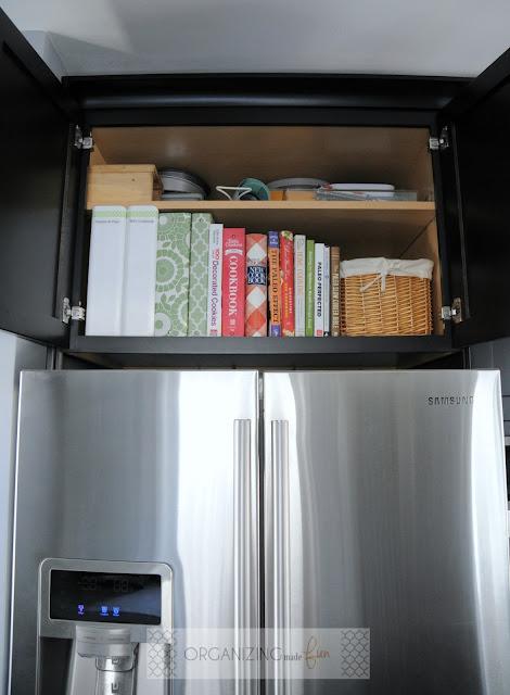 Organized cupboard over fridge for cookbooks and baking supplies :: OrganizingMadeFun.com