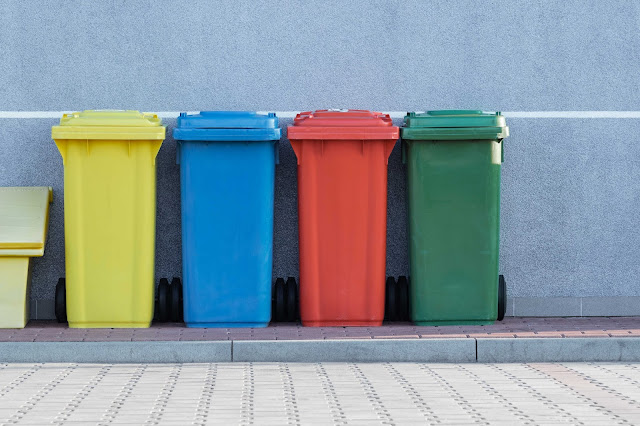Different coloured wheelie bins lined up against a wall