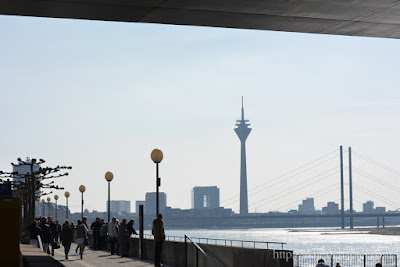 Düsseldorf promenade, by the river Rhine, with people standing looking over water.
