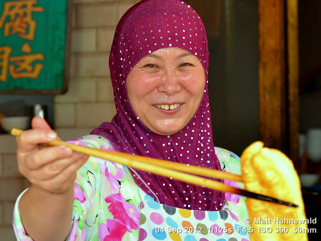 street portrait, headshot, China, Xi'an, Hui Muslims, Hui Muslim woman, headscarf, yóutiáo, oil-fried breadstick, Chinese cruller