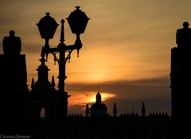 Закат в Царицыно, солнце в куполе церкви. Силуэт ограды и фонаря.