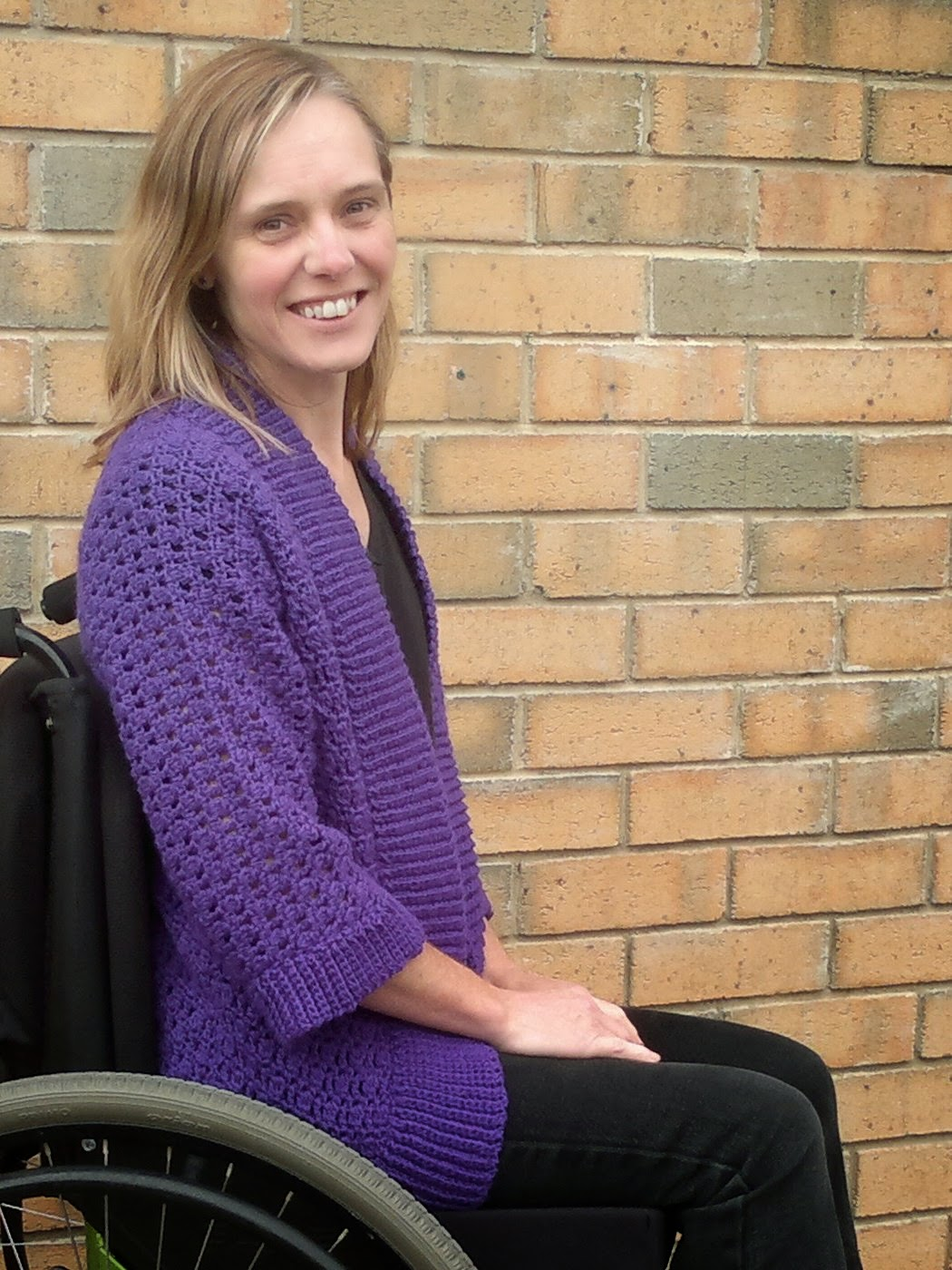 Right hand side view of the Belcarra cardigan when seated. Jodie is sitting in her wheelchair.