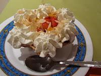 Tulipa de frutas frescas, nata y láminas de coco garapiñado