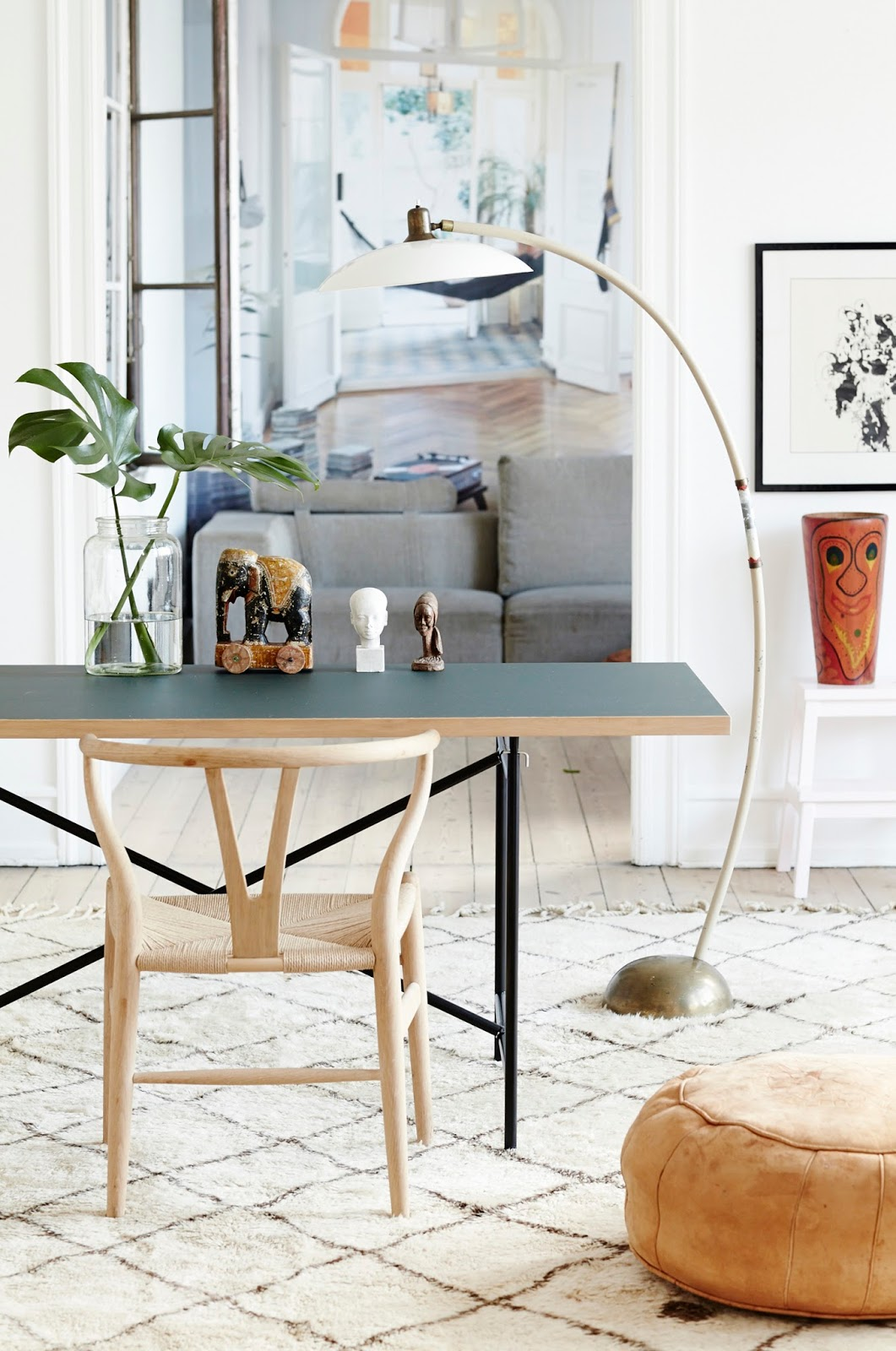 bohemian scandinavian apartment with moroccan rugs, wall art and design furniture , dining table, wishbone chair, monstera plant
