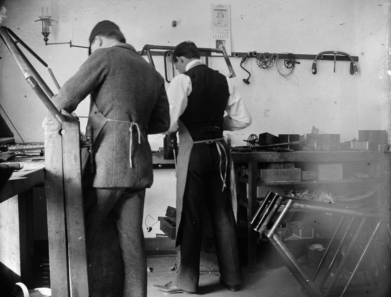 Orville Wright and Edwin H. Sines, neighbor and boyhood friend, filing frames in the back of the Wright bicycle shop in 1897.