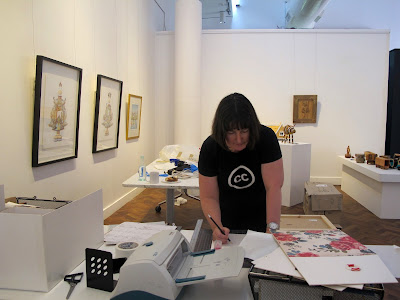 Woman in a gallery during install, marking something with a pencil on  a table in the middle of the gallery.