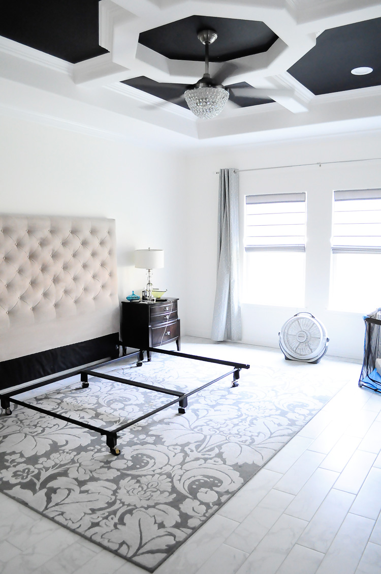 White master bedroom with black tray ceiling and tall tufted upholstered headboard.