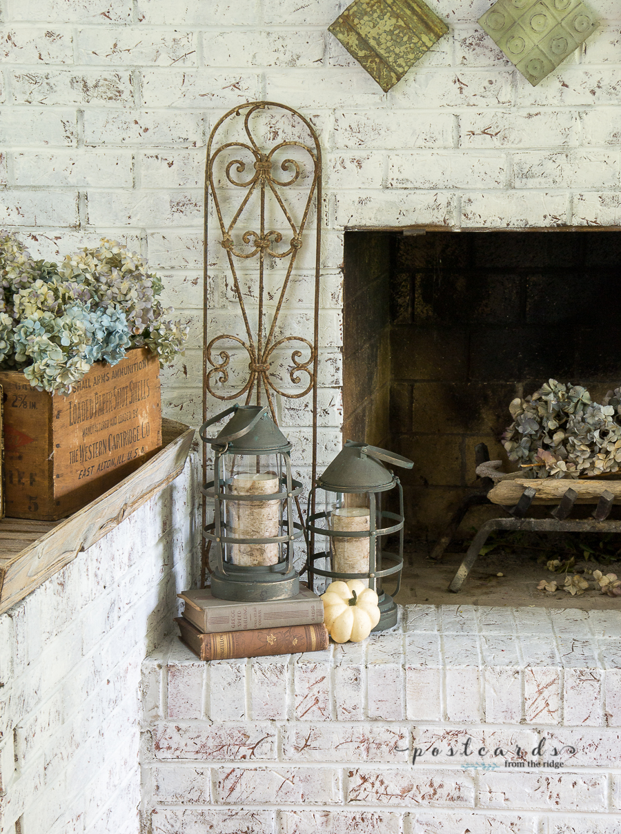 metal lanterns on white brick hearth