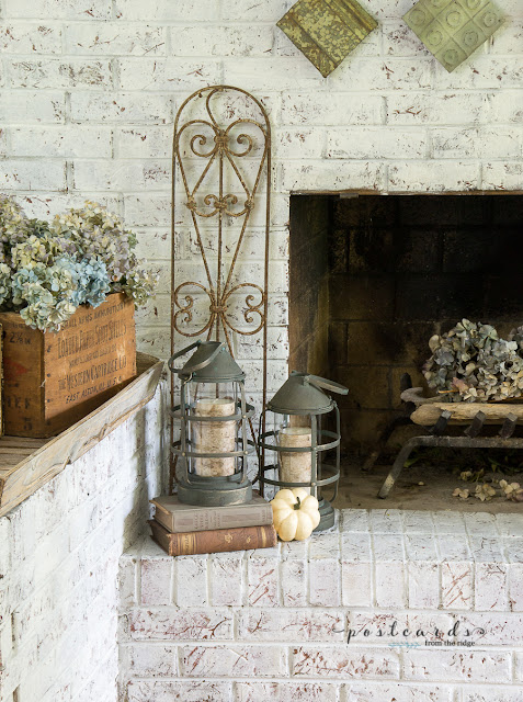 white brick fireplace with dried hydrangeas, old rusty fence section, books, metal lantern, and faux pumpkins