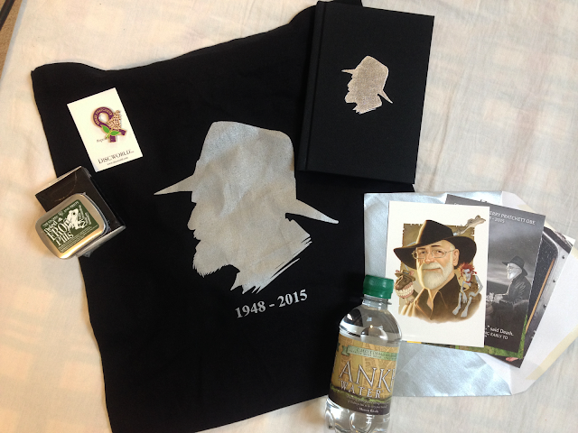 Terry Pratchett Memorial gift bag - Ankh Water, Dried Frog Pills, story collection, postcards, purple ribbon pin, and black canvas bag