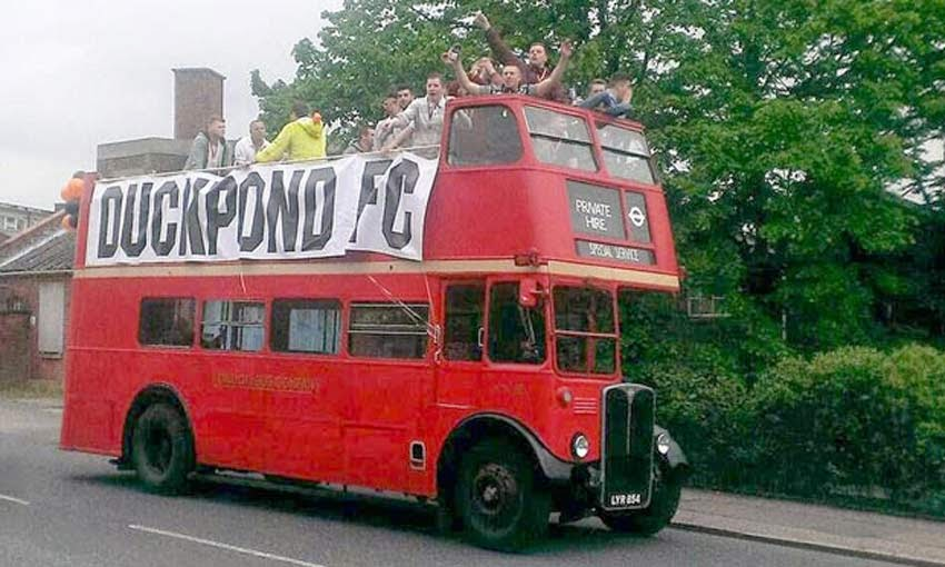 Old school double decker bus, banner states DUCKPOND FC with the team cheering from the open top.