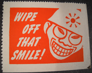 "A poster featuring a racist caricature of a smiling Japanese man with the text ""Wipe off that smile!"""