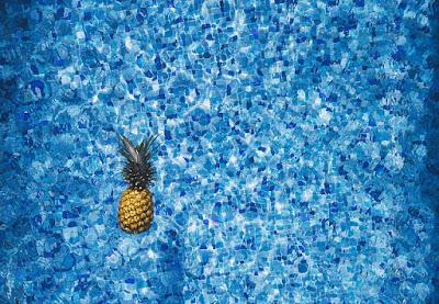 Ananas qui flotte dans une piscine tapissée de mosaïques.