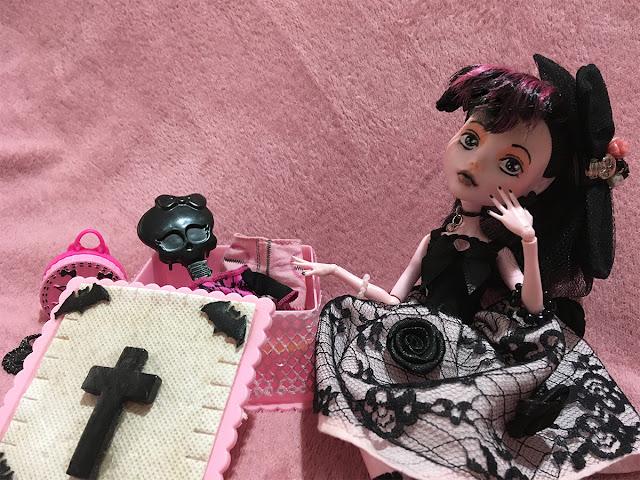 boneca draculaura com seus itens fofos olhando pra câmera