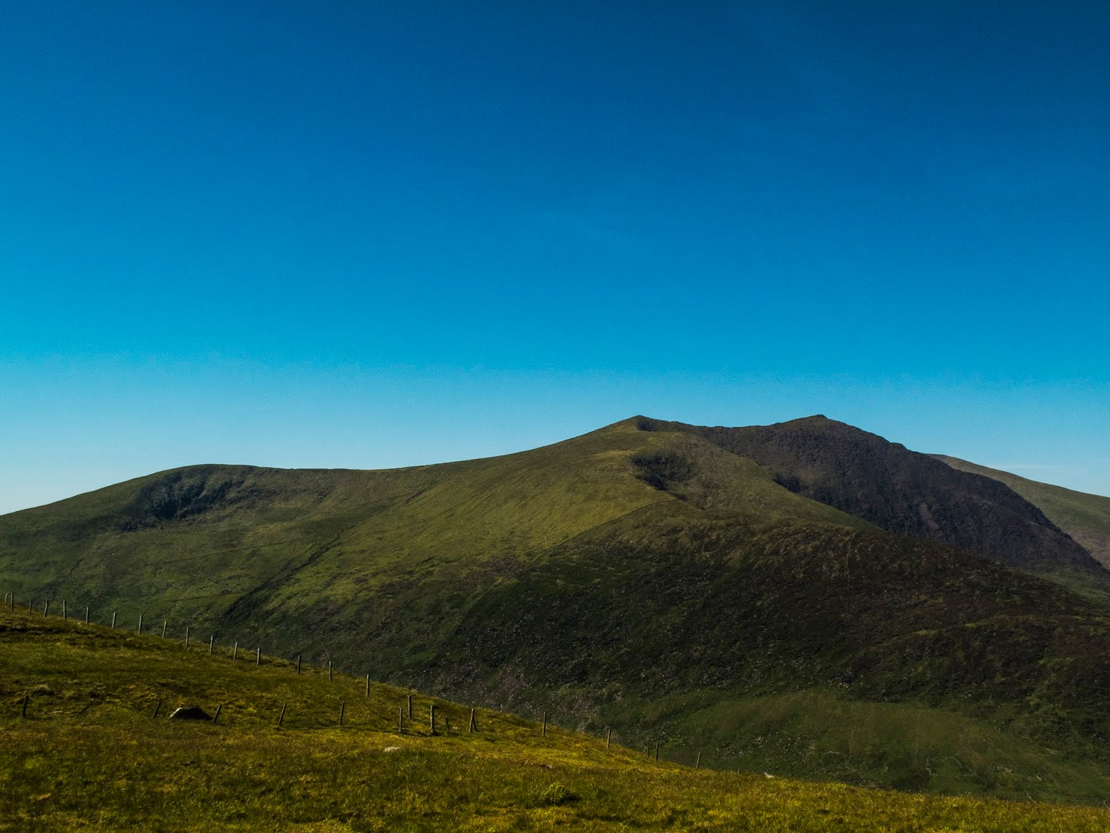 Mountain side views from Conor Pass in the Dingle Peninsula on a sunny day with blue skies.