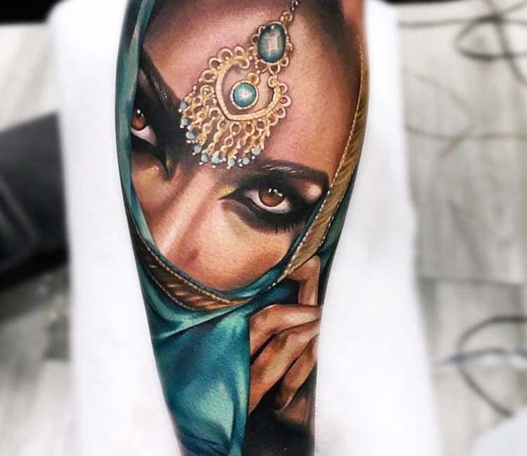Tatuaje de un rostro de mora tapándose la boca con velo