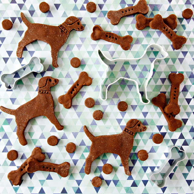Brown dog treats shaped like dogs, bones, and small circles