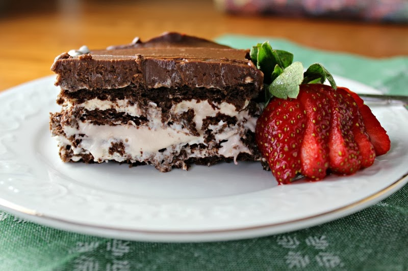 Chocolate-Strawberry Eclair Cake piece on plate with strawberry garnish close up