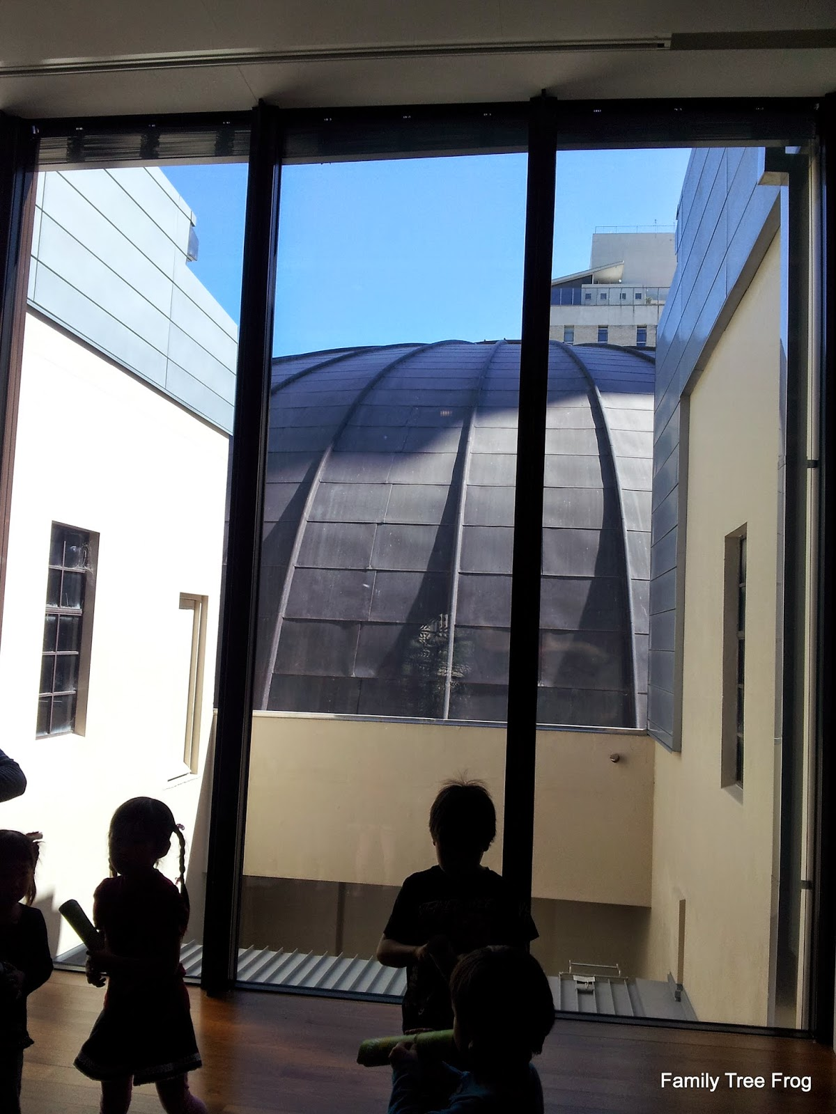silhouettes of children in Museum of Brisbane looking out at dome of City Hall