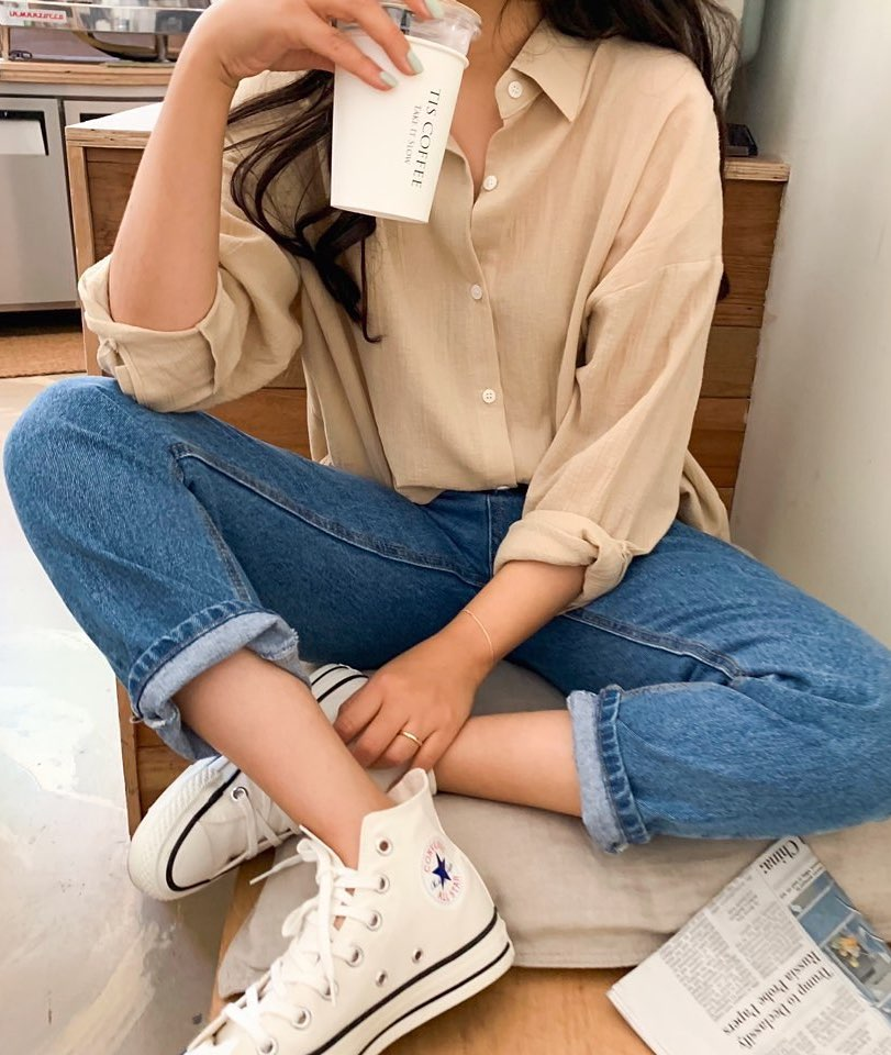 Easy denim look with neutral button-down shirt, straight-leg jeans, and hi-top Converse sneakers