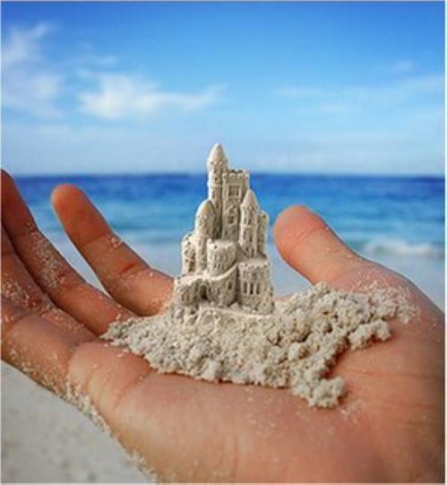 #PraCegoVer: Castelo de areia construído na palma da mão.