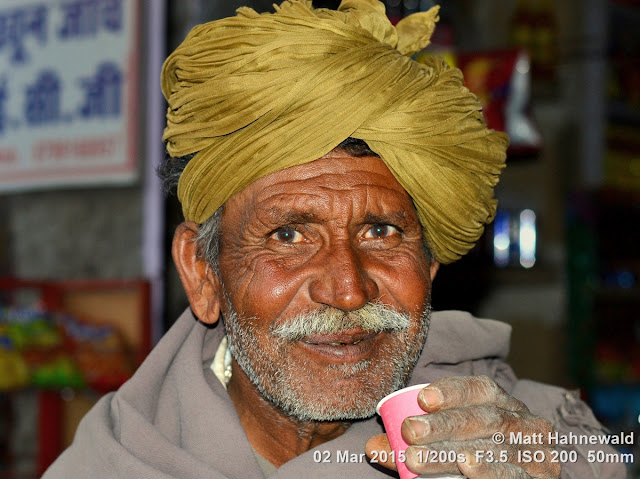 Rajasthani turban; pagari; drinking; milk tea; chai; moustache; yellow turban; left hand; Matt Hahnewald Photography; Facing the World; photography; photo; image; outstanding; fantastic; favourite; superior; excellent; inspirational; vibrant; breathtaking; Nikon D3100; Nikkor AF-S 50mm f/1.8G; prime lens; 50mm; 4 : 3 aspect ratio; horizontal format; closeup; portrait; portraiture; headshot; en face; front view; outdoor; colour; colourful; world cultures; cultural; character; personality; real people; human; human head; human face; human eyes; facial expression; eye contact; Rajasthani pagari; turban; consent; empathy; rapport; encounter; relationship; emotion; mood; environmental portrait; ethnic portrait; travel; travel portrait; travel destination; tradition; Jaisalmer; Rajasthan; India; one person; male; adult; Indian man; posing; authentic; incredible; awesome; colour yellow; lived-in face; wrinkles; Rajasthani man; street portrait