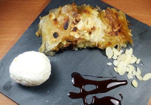 Un plato con una bola de helado, apfelstrudel y almendras fileteadas