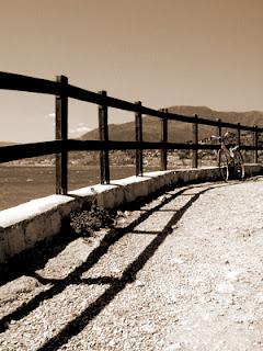 [bici vicino ad un guard rail o barriere, tutto in scala di griggio]