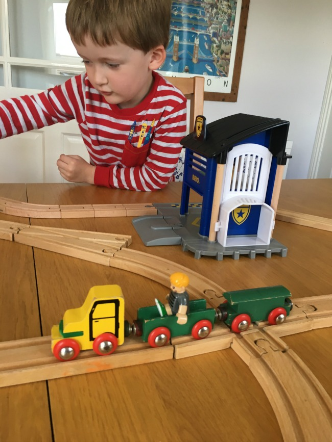 Boy-playing-with-Brio-police-station-and-old-versions-in-foreground