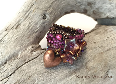 Be Mine freeform peyote ring by Karen Williams with three bellflower pressed glass beads and a puffed heart charm