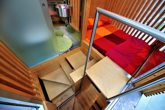 Photo of the narrow wooden staircase to the small bedroom level