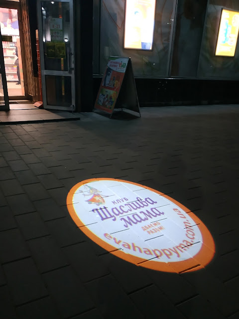 Световая реклама на тротуаре.