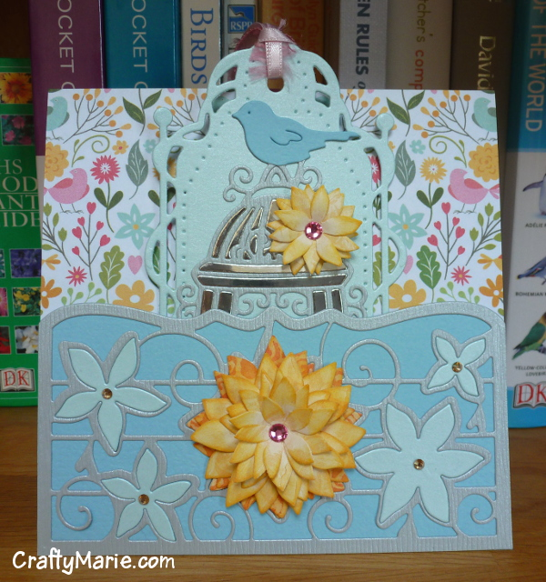 Birdcage bird handmade greeting card with tag in pale blue, pink and orange colors made with Tonic Studio dies