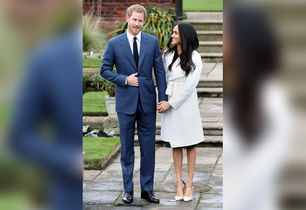 Prince Harry standing next to a man in a suit and tie: Prince Harry and Meghan Markle appear during an official photocall to announce their engagement at The Sunken Gardens at Kensington Palace in London on Nov. 27, 2017.