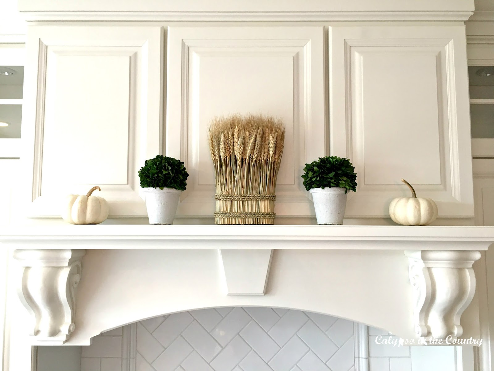White Stove Mantel Decorated with White Pumpkins, topiaries and wheat - white pumpkin vignettes