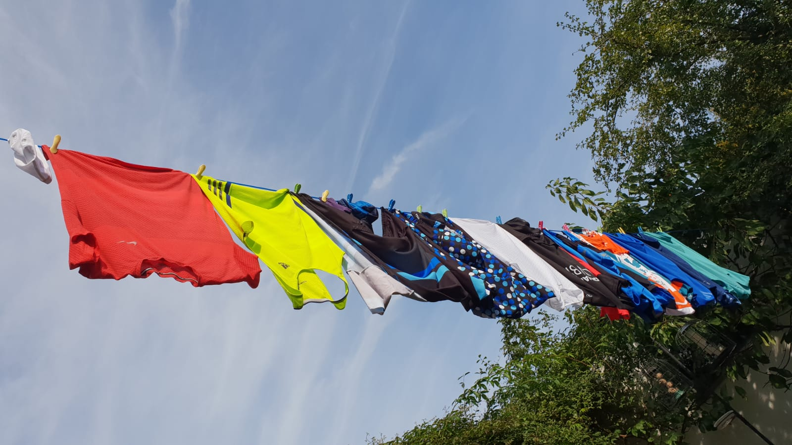 Brightly coloured cycling tops on a washing line