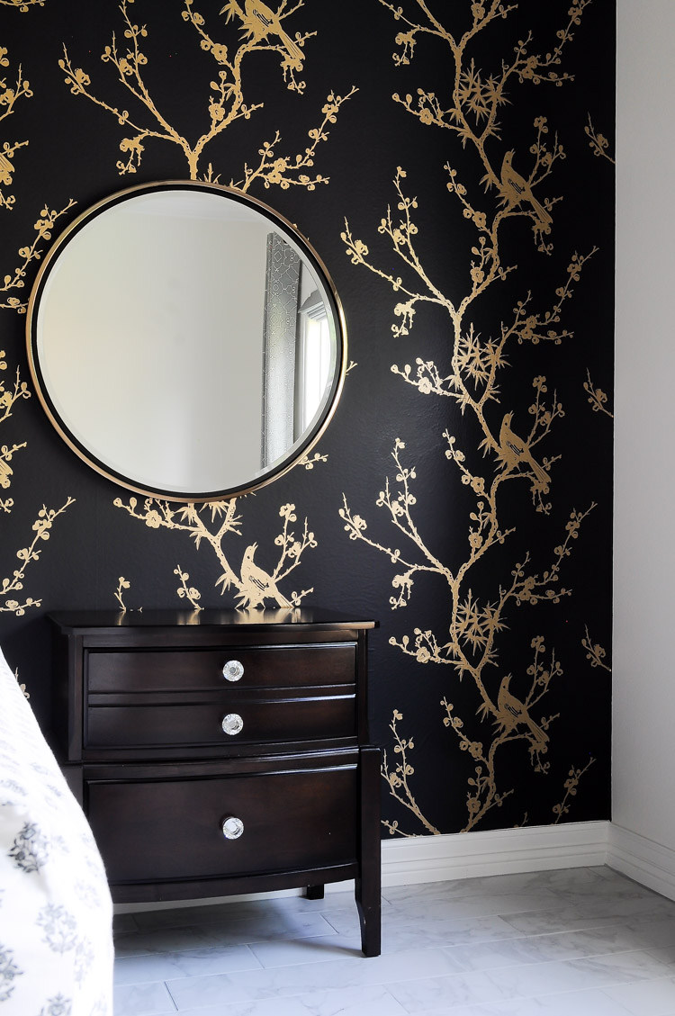 The Wais mirror by Holly & Martin adds a touch of glamour to this dramatic black and gold master bedroom. Simply stunning! The wallpaper is bird watching by Cynthia Rowley for Tempaper.
