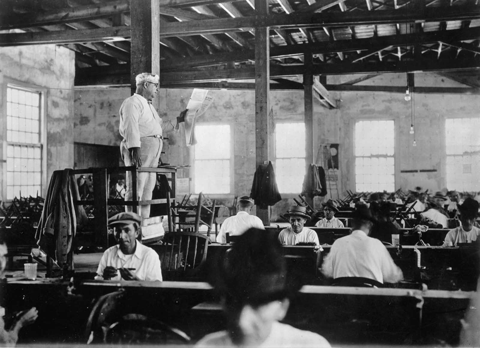 A lector reads a newspaper to workers in a Key West, Florida cigar factory. 1930.