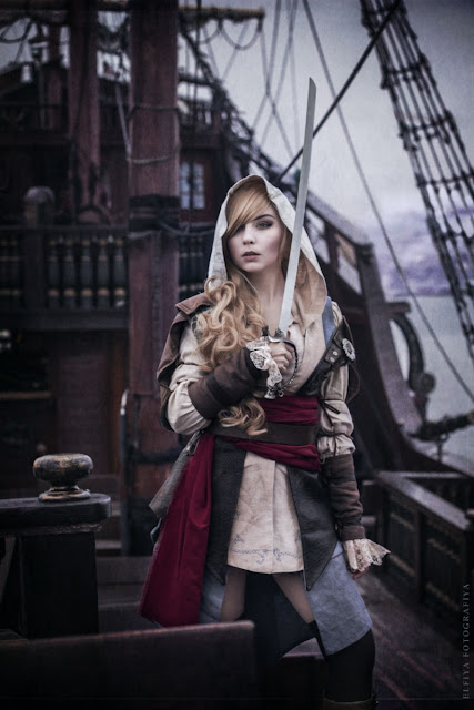 This woman is dressed as a female steampunk pirate (lady pirate). Clothing: hooded shirt, jacket, red sash, belt, boots. Women's steampunk pirate costume. wench/buncaneer